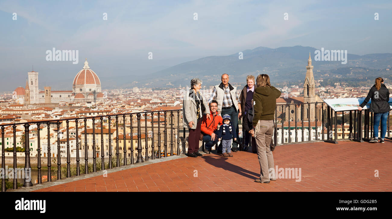 A family of tourists posing for photos on the Piazzale Michelangelo, while another looks at the interpretative board. - Stock Image