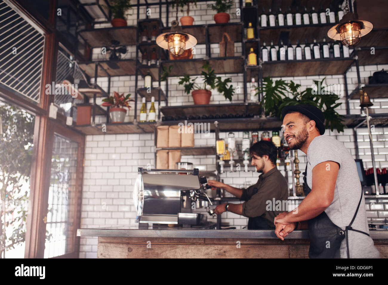 Coffee shop owner standing at the counter, with barista working in background. - Stock Image