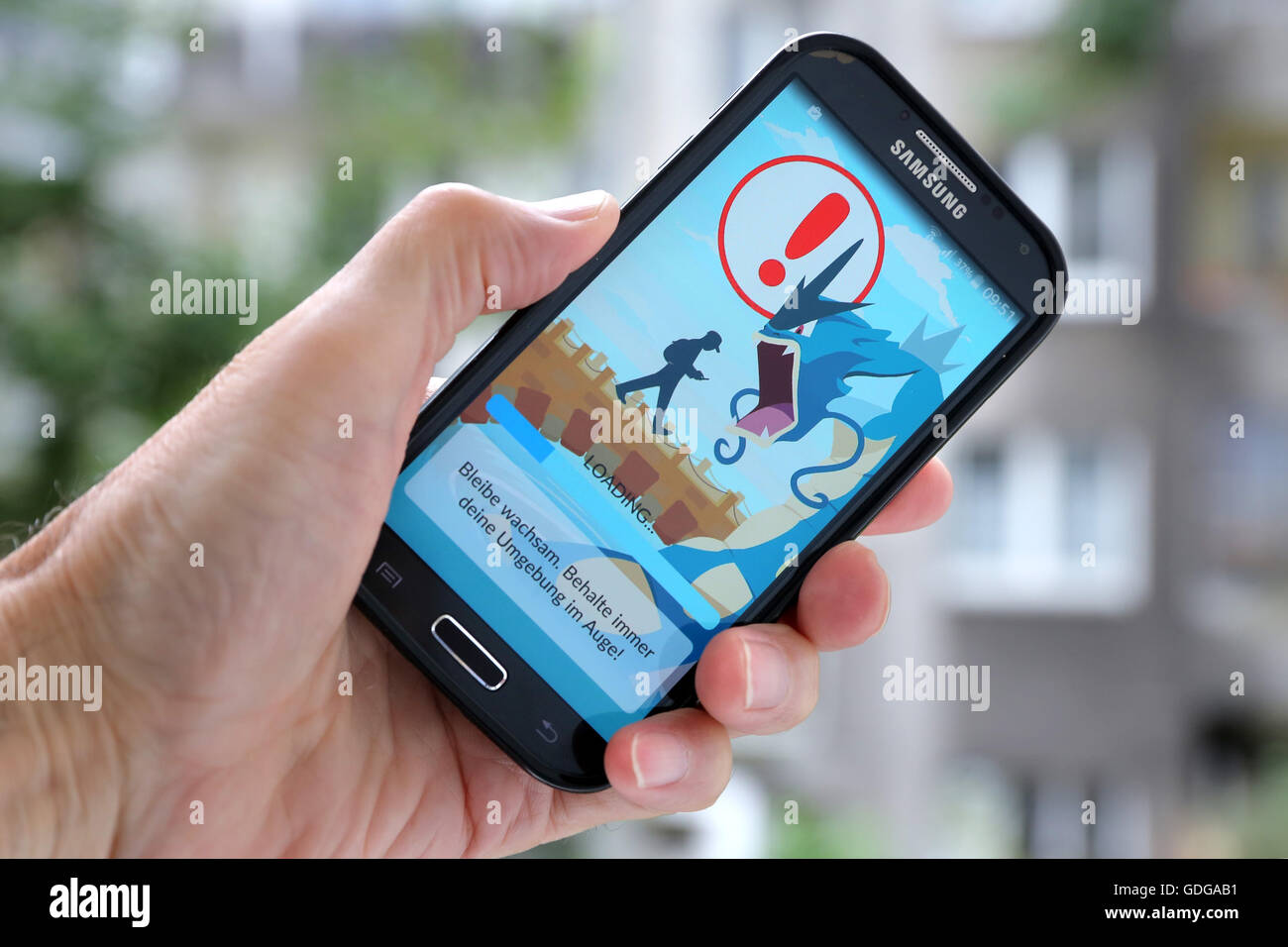 """German version of the latest Nintendo game """"Pokémon go"""" on a Samsung smartphone. The caution advises players to be aware of the surroundings while playing Pokemon Go. Dortmund, Germany, July 17th.2016 Stock Photo"""