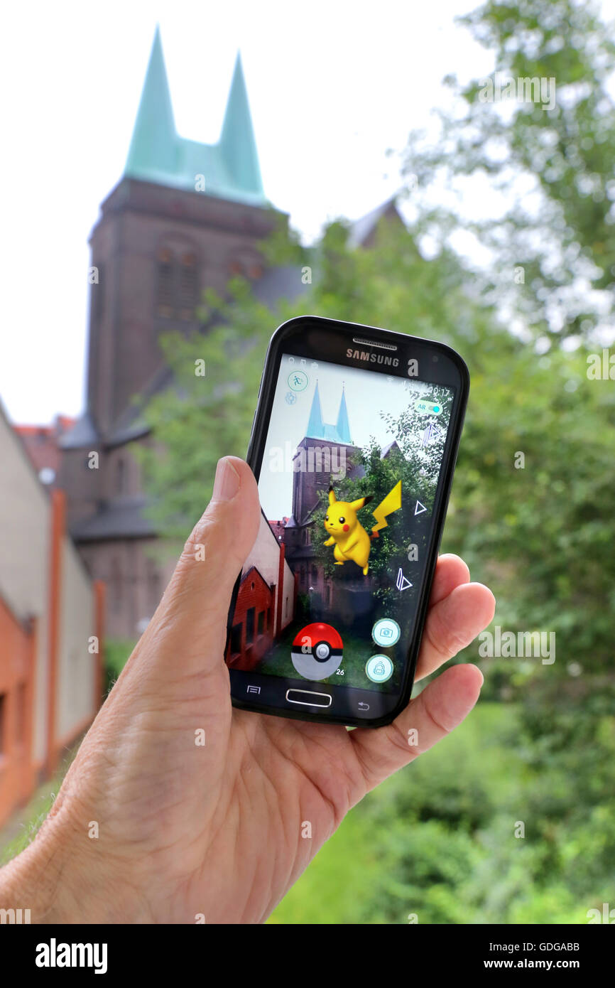 """German version of the latest Nintendo game """"Pokémon go"""". Pokemon monster in the garden of the church on a smartphone of a player. Dortmund, Germany, July 17th.2016 Stock Photo"""
