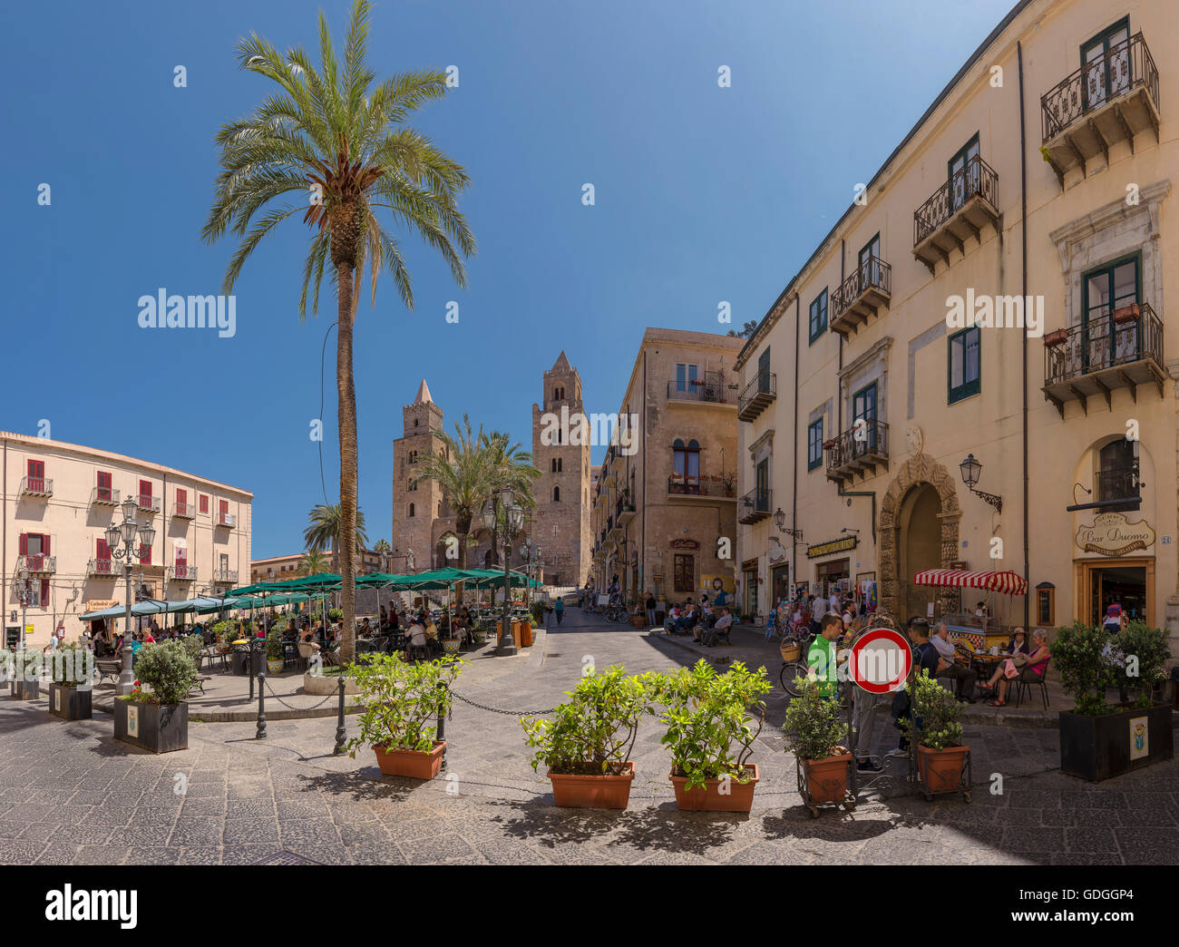 Square with outdoor cafes,sunshades and palm trees,Cefalu cathedral - Stock Image