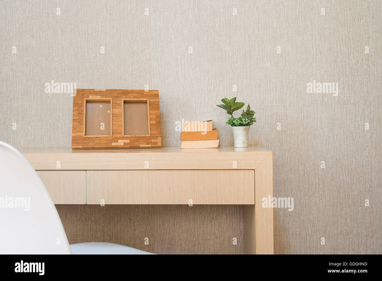 Home interior decor, bouquet of lilacs in a vase,picture frame and books on rustic wooden table, on wallpaper background. - Stock Image