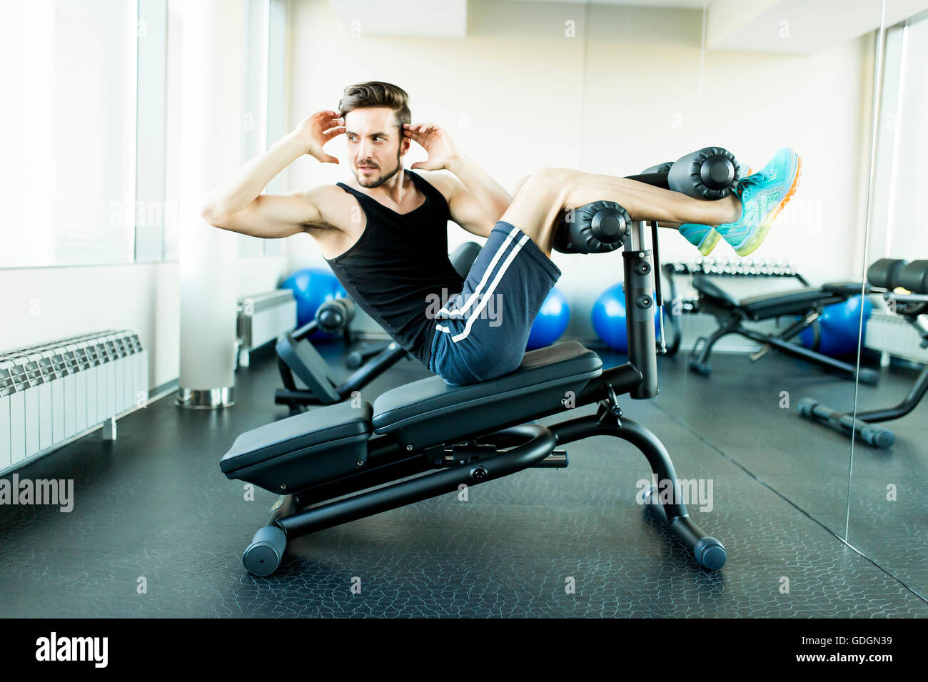 Young man doing exercises for abdominal muscles at the gym - Stock Image