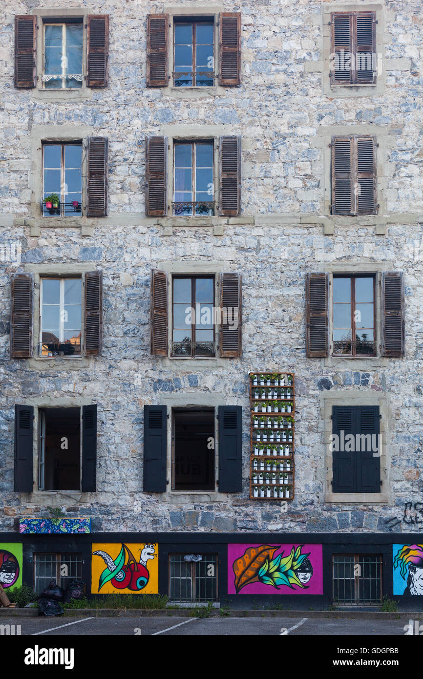 Inner city stone apartment building with a wall planter for flowers and herbs - Stock Image