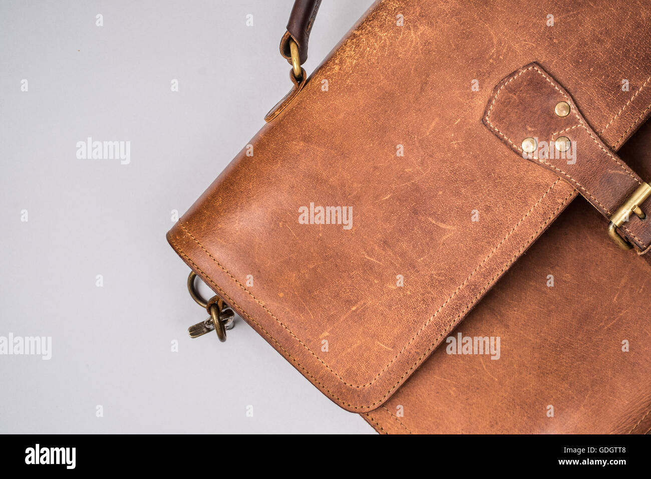 Brown Vintage leather briefcase with strap and brass buckle, - Stock Image
