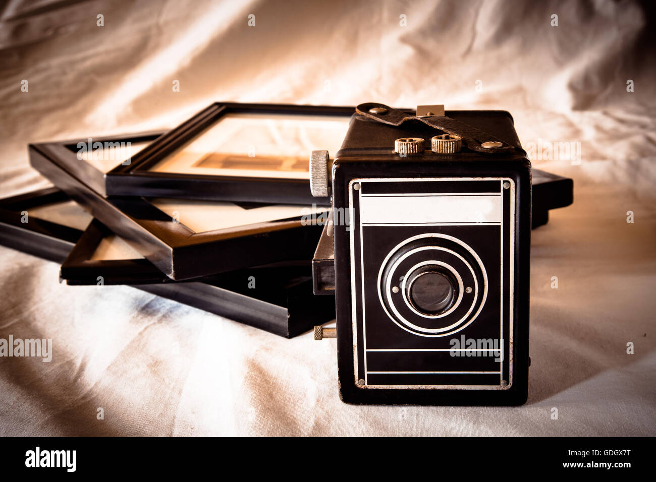 Vintage style film box camera with framed photographs and retro tone - Stock Image