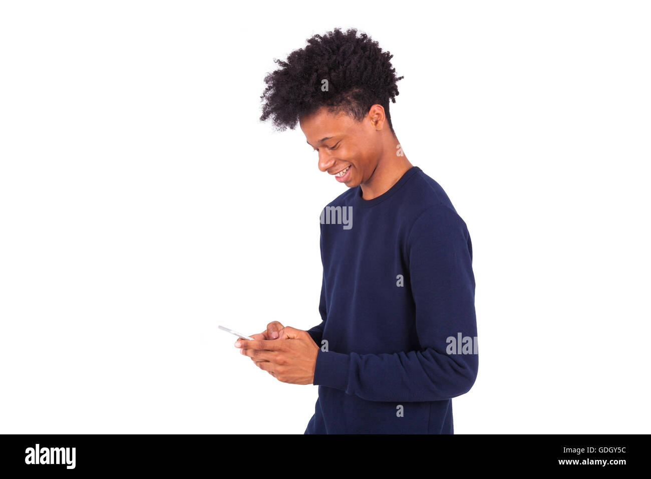 Young African American man sending a sms text message on his smartphone - Black teenager people - Stock Image