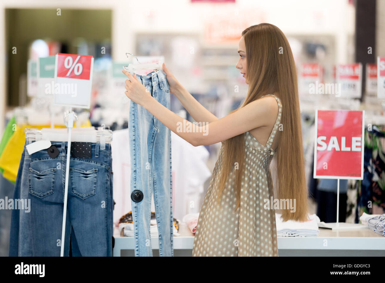 893c859d5c Profile portrait of long-haired young pretty woman in shopping centre store  choosing clothes looking at jeans and thinking