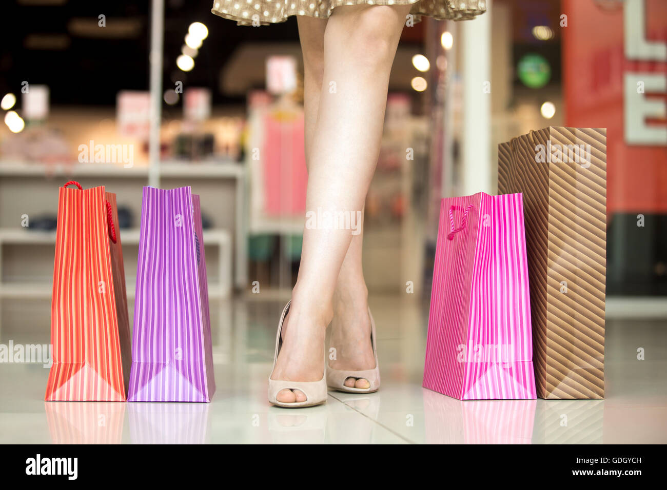Close-up of woman crossed beautiful legs standing in shopping centre in front of clothing store with colorful shopping - Stock Image