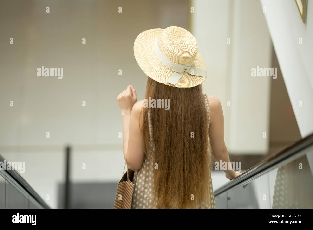 Young beautiful long-haired customer woman wearing a hat and cute polka dot summer dress carrying shopping paper - Stock Image