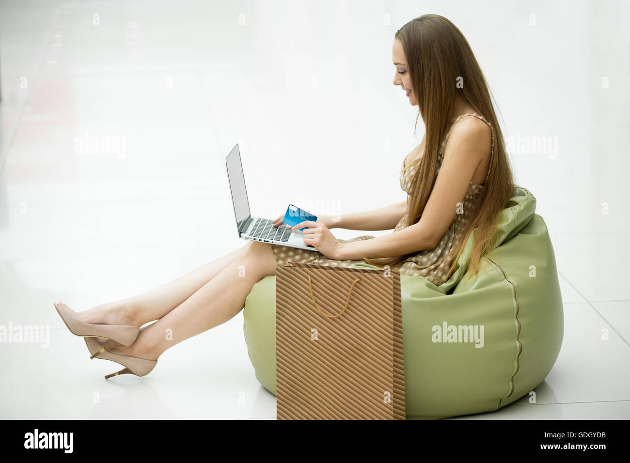 Full-length side view portrait of young smiling pretty woman sitting in shopping centre on bean bag chair with laptop - Stock Image