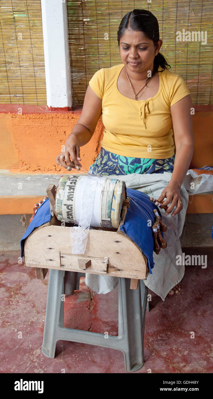 Woman making lace by hand, using bobbins and a roller. She comes from a family historically skilled in lacemaking. - Stock Image