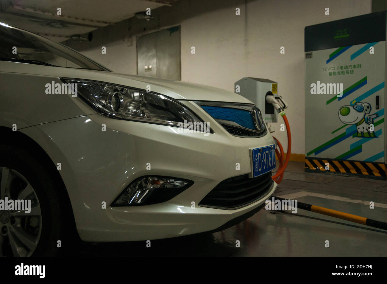 A Chang'an Eado EV in front of a standing twin fast charger in an underground car park in Chongqing, China - Stock Image