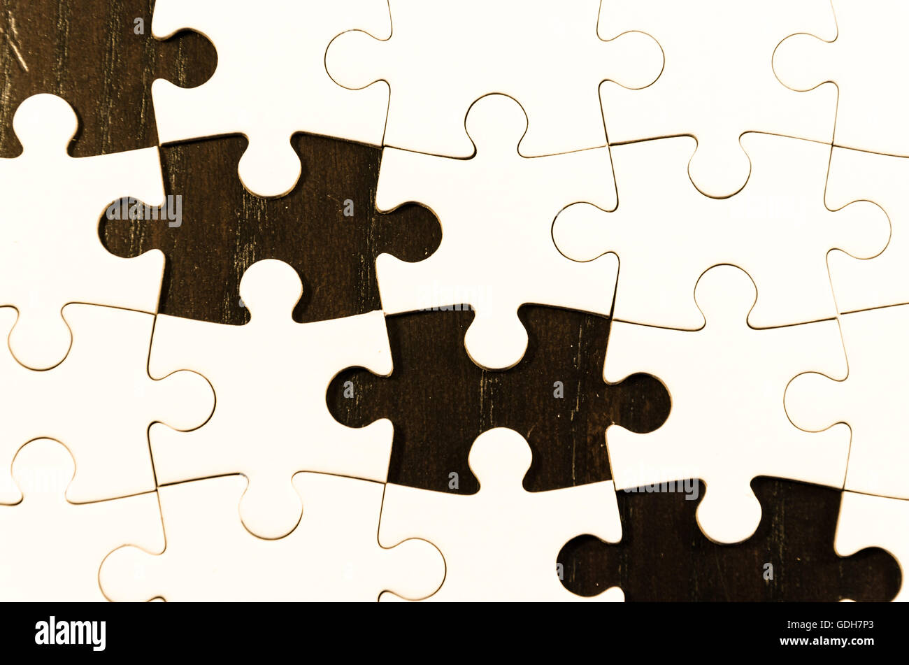 white jigsaw/puzzle white some gaps over  black wooden table background, symbol of problem solving - Stock Image