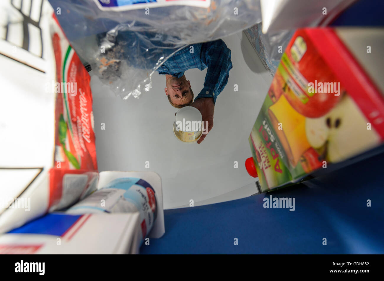 : Man throws an empty packaging in a trash can , view from the trash, , , - Stock Image