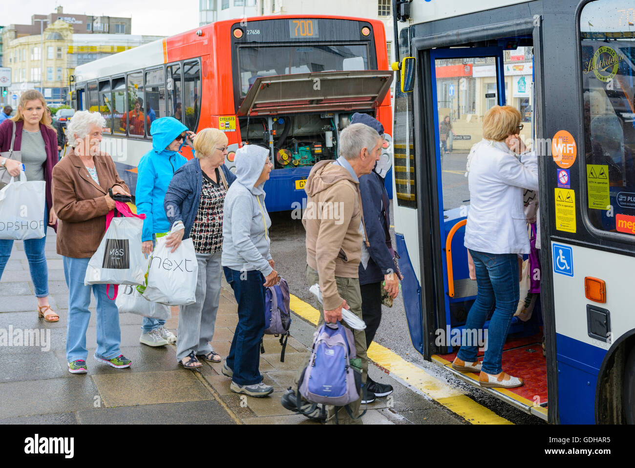 Queue of people boarding a Stagecoach bus in the UK. - Stock Image