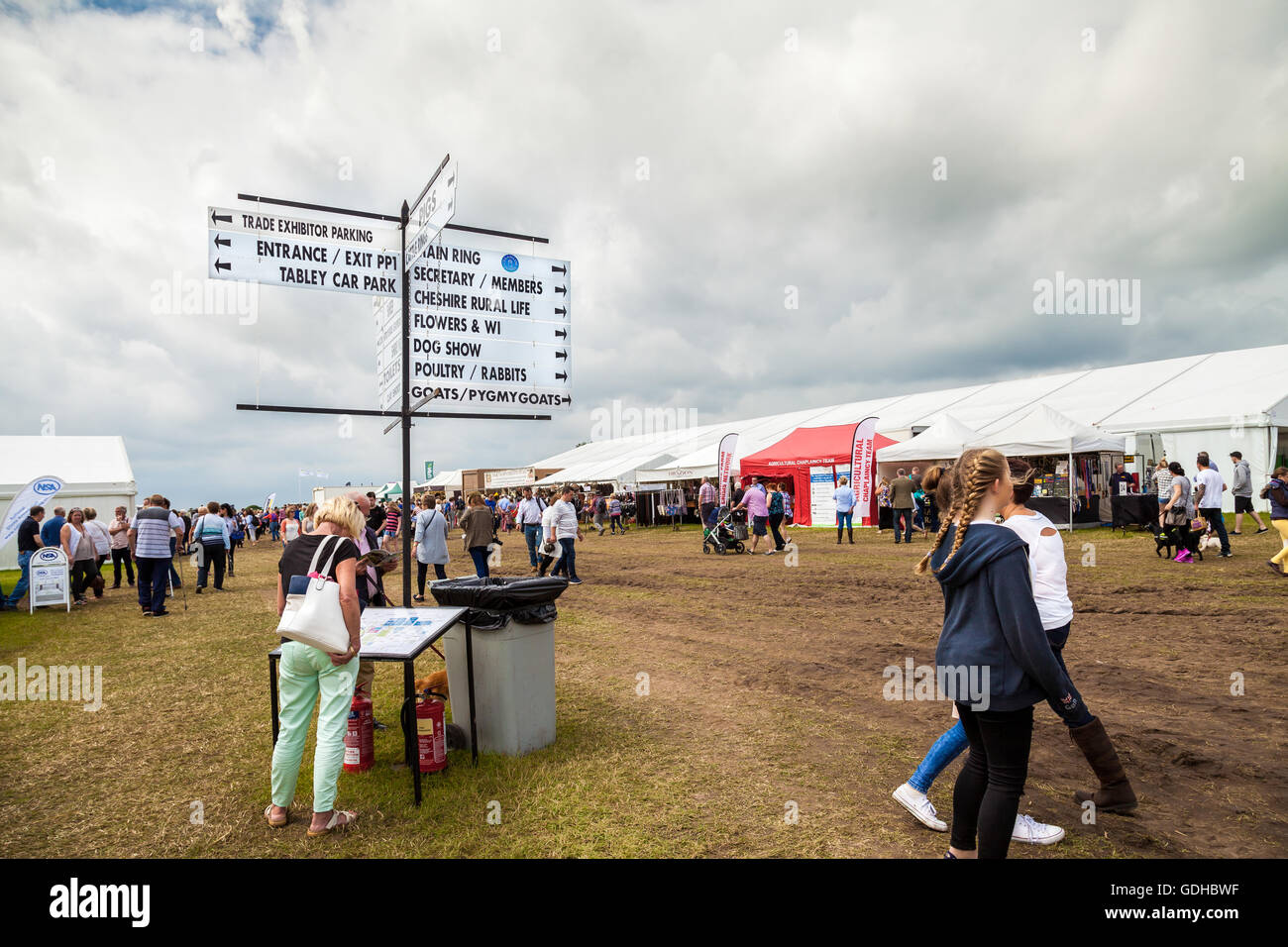 Woman looking at map below a  sign post with directions to exhibits at he Royal Cheshire Show. UK 2016 - Stock Image