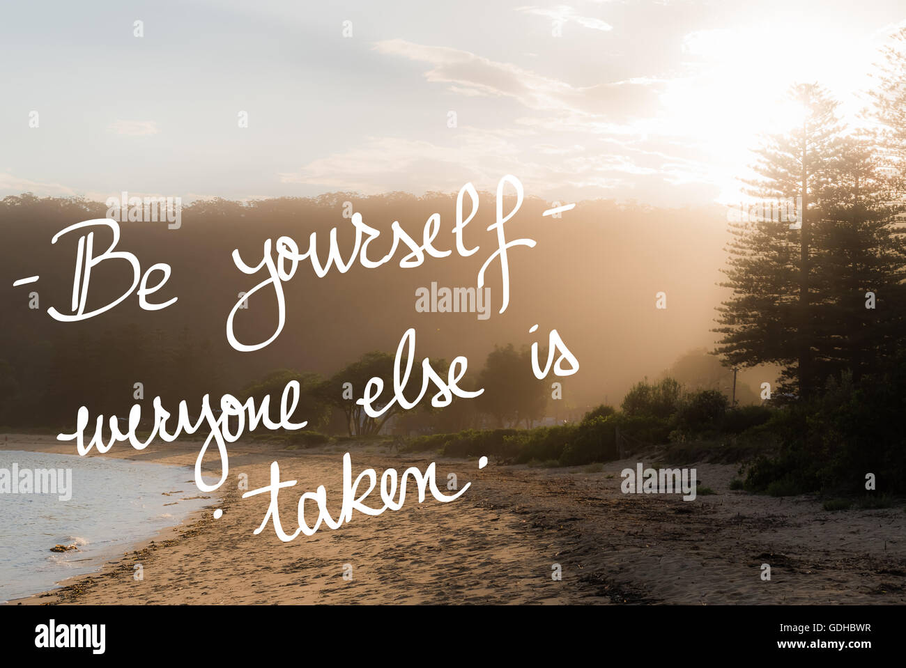 Be Yourself, Everyone Else Is Taken message. Handwritten motivational text over sunset calm sunny beach background - Stock Image