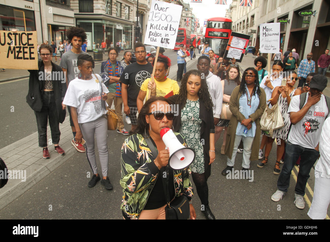 London, UK. 17th July, 2016.: Ava Moran speaks about Mzee Mohammed through a mega phone on Oxford Street. Black - Stock Image