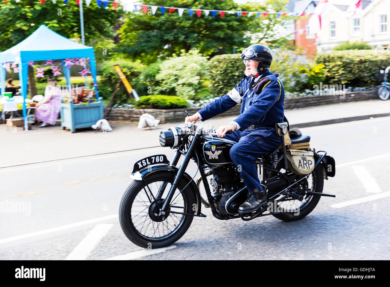 Old man riding motorbike on road down street vintage bike unsafe danger dangerous scary - Stock Image
