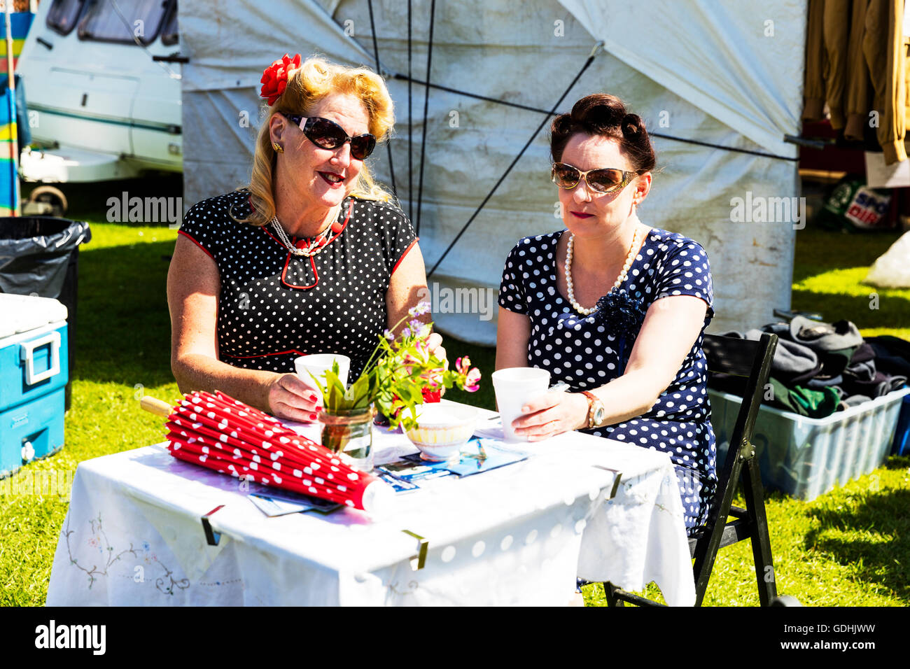 English tea outside 2 women drinking tea wearing polker dot dress dresses 1940's style traditional dress attire - Stock Image