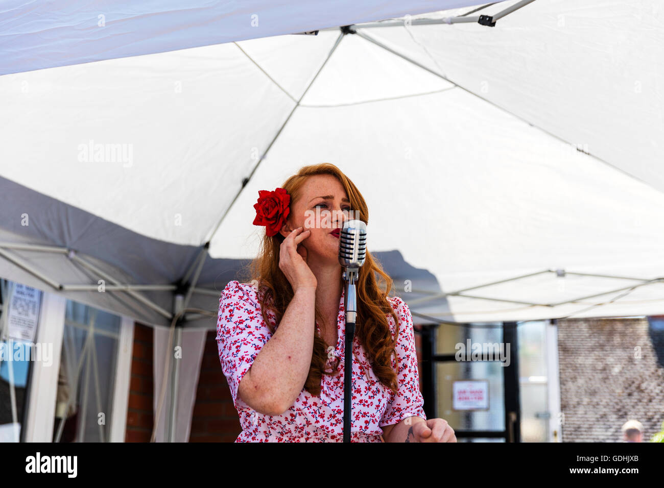 Woman singer singing into microphone 1940's style dress hair Woodhall Spa 1940's weekend people ww2 style - Stock Image
