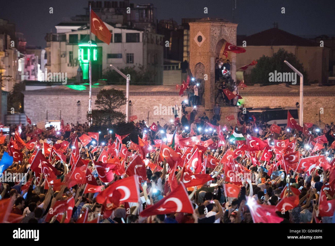 Istanbul, Turkey. 17th July, 2016. People shout slogans and hold flags during a demonstration at Taksim Square in Stock Photo