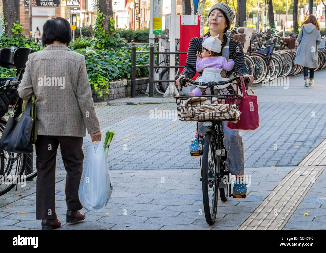 Mother with child cycling in the city of Osaka Japan along cycle paths which are generally kept separate from road - Stock Image