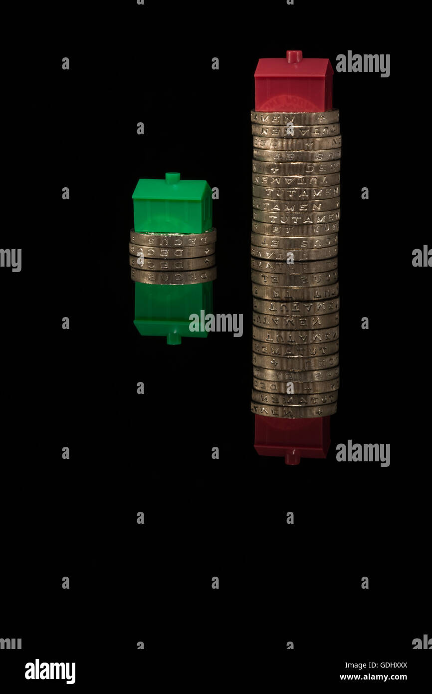 House / housing / property price inflation concept. Colorful toy houses placed on stacks of pound coins on black Stock Photo
