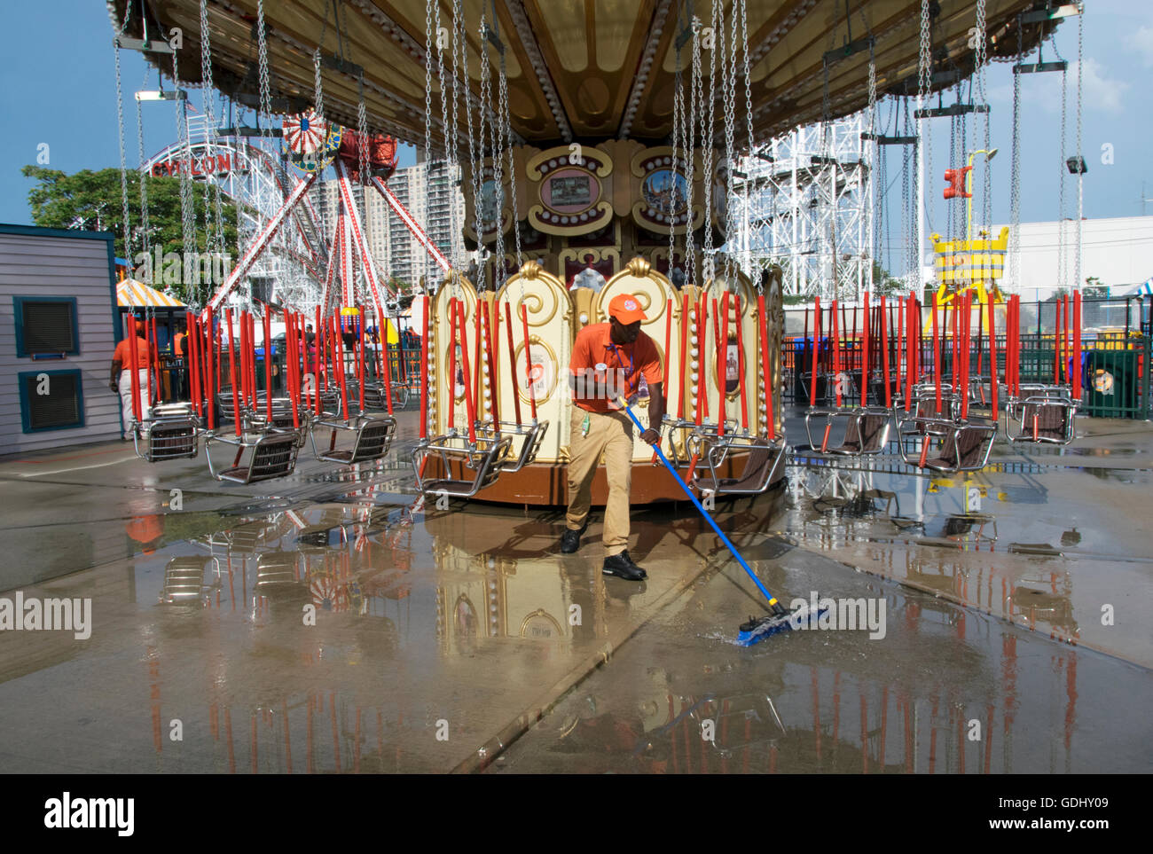 A worker clears puddles after a summer rain at Lynn's Trapeze, a ride in Luna Park in Coney Island, Brooklyn, - Stock Image