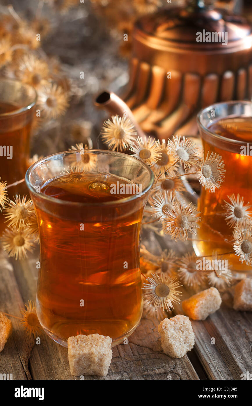 Cups of tea and copper teapot among dry flowers - Stock Image