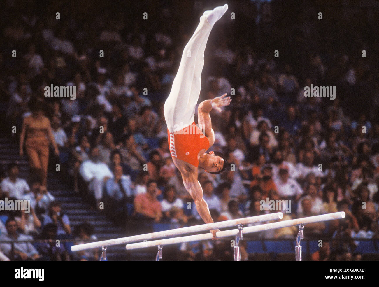 Fei Tong of China performs on parallel bars at 1984 Olympic Games in Los Angeles. - Stock Image