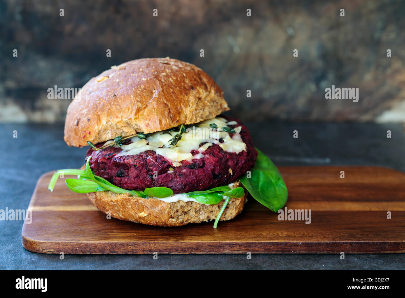 Beetroot and black bean burger with melted cheese and thyme - Stock Image