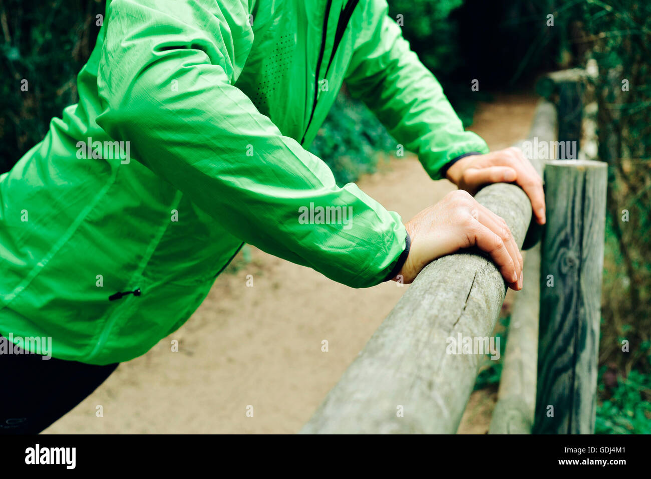 closeup of a young caucasian sportsman wearing sport clothes doing incline push-ups outdoors - Stock Image