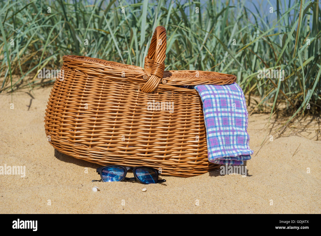 Picnic basket with blue white checkered napkin and sunglasses on sandy beach. Weekend break concept - Stock Image