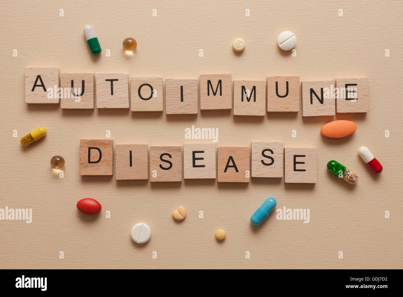 The word autoimmune disease formed with wooden letters and pills around - Stock Image