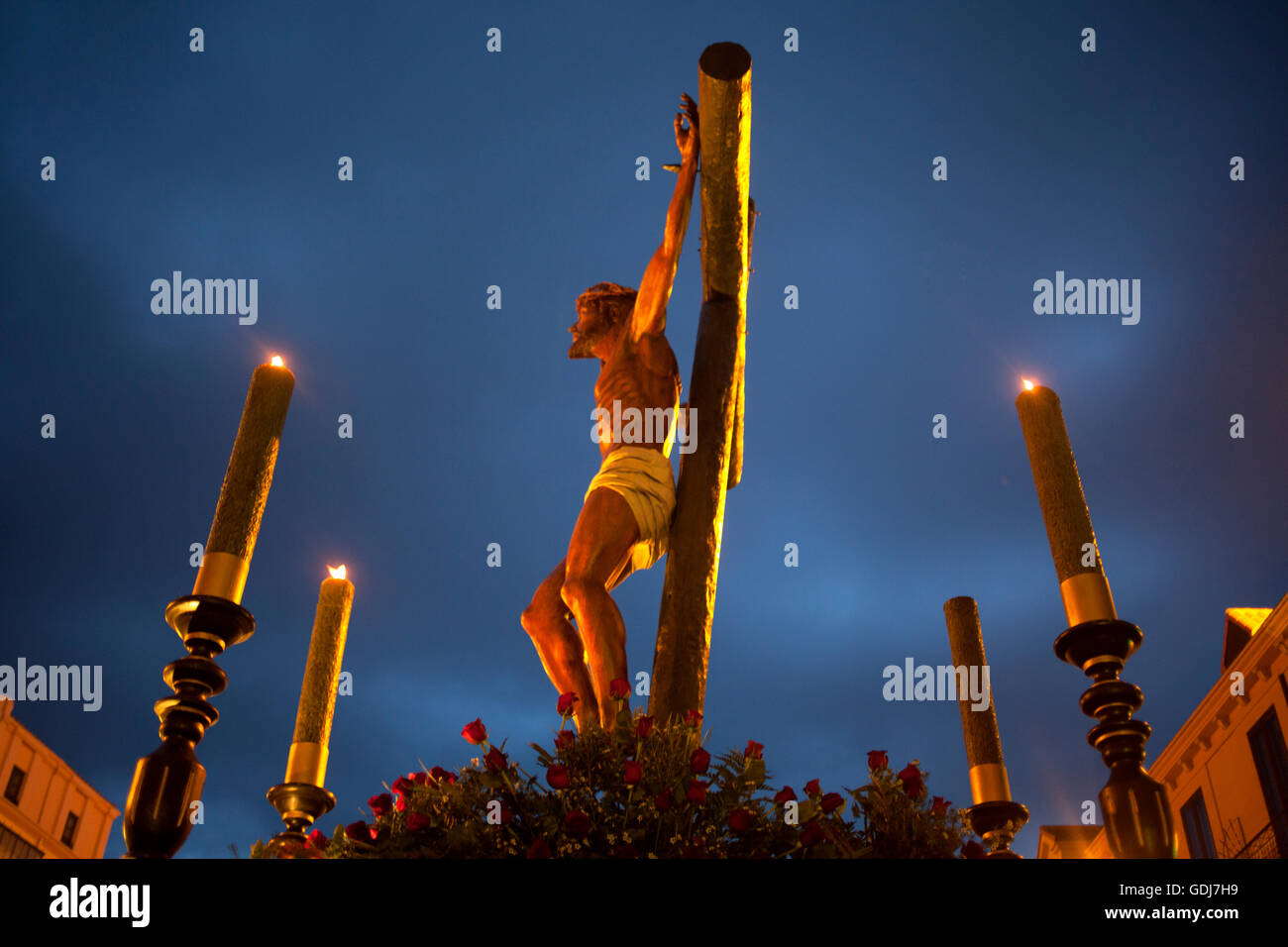 An Image Of Jesus Christ Crucified Decorated With Four Candles During Easter Holy Week Procession
