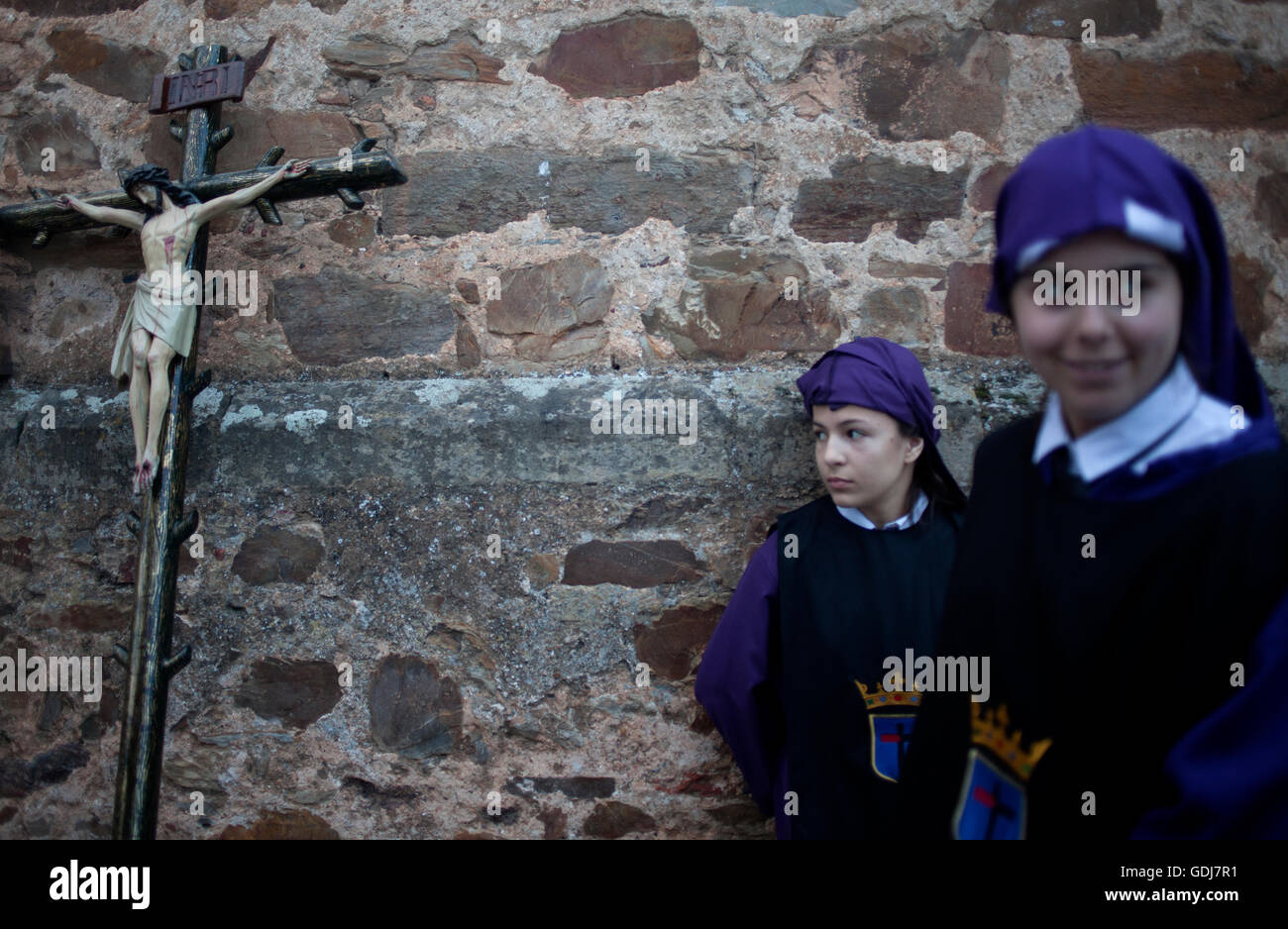 Young teenagers stand by a crucifix during an Easter Holy Week procession in Astorga, Castilla y Leon, Spain. - Stock Image