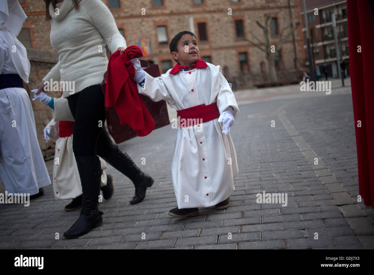 A boy dressed as a penitent holds his mother´s hand during an Easter Holy Week procession in Astorga, Castilla - Stock Image