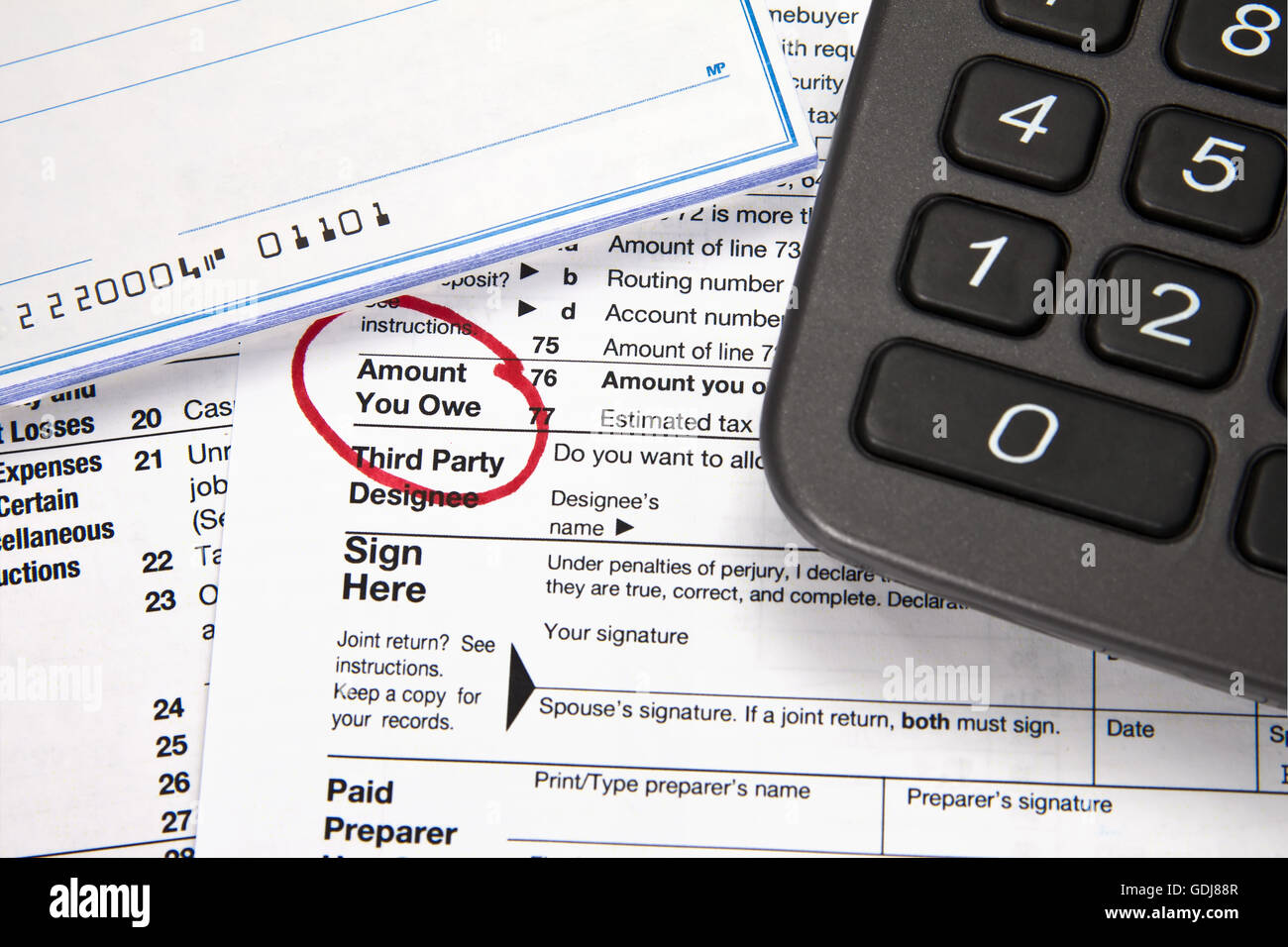 Tax document - Amount you owe on tax return with checkbook and calculator - Stock Image