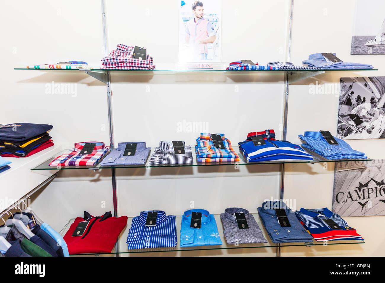 Shirts on shelf in clothes shop display displaying shirts for men to choose shirt on shelve UK England - Stock Image