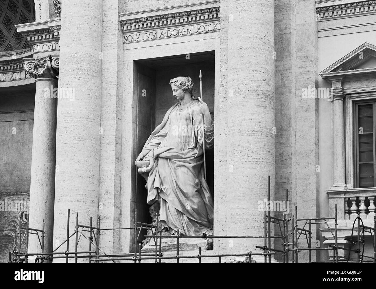 Statue of Salubrity holding a cup from which a snake is drinking and scaffolding on the Trevi Fountain Piazza di - Stock Image