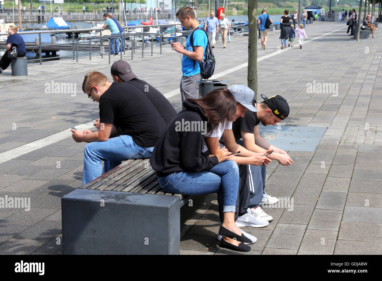 POKEMON GO, young people play the new Nintendo game Pokémon go on their smartphones on Lake Phoenix in Dortmund, Germany. The players try to catch in the real world virtual Pokemon monsters on to their smartphone devices. Stock Photo
