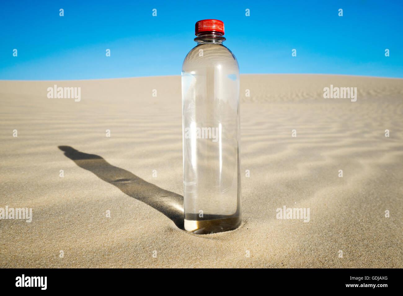 PET water bottle in desert landscape - Stock Image