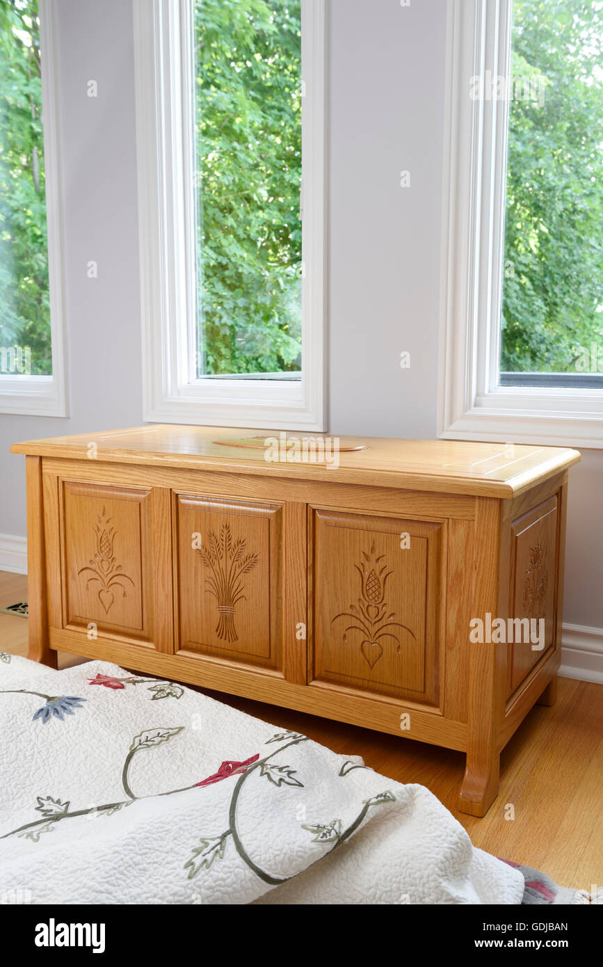 Carved oak cedar chest with trees through windows and blanket in bedroom - Stock Image