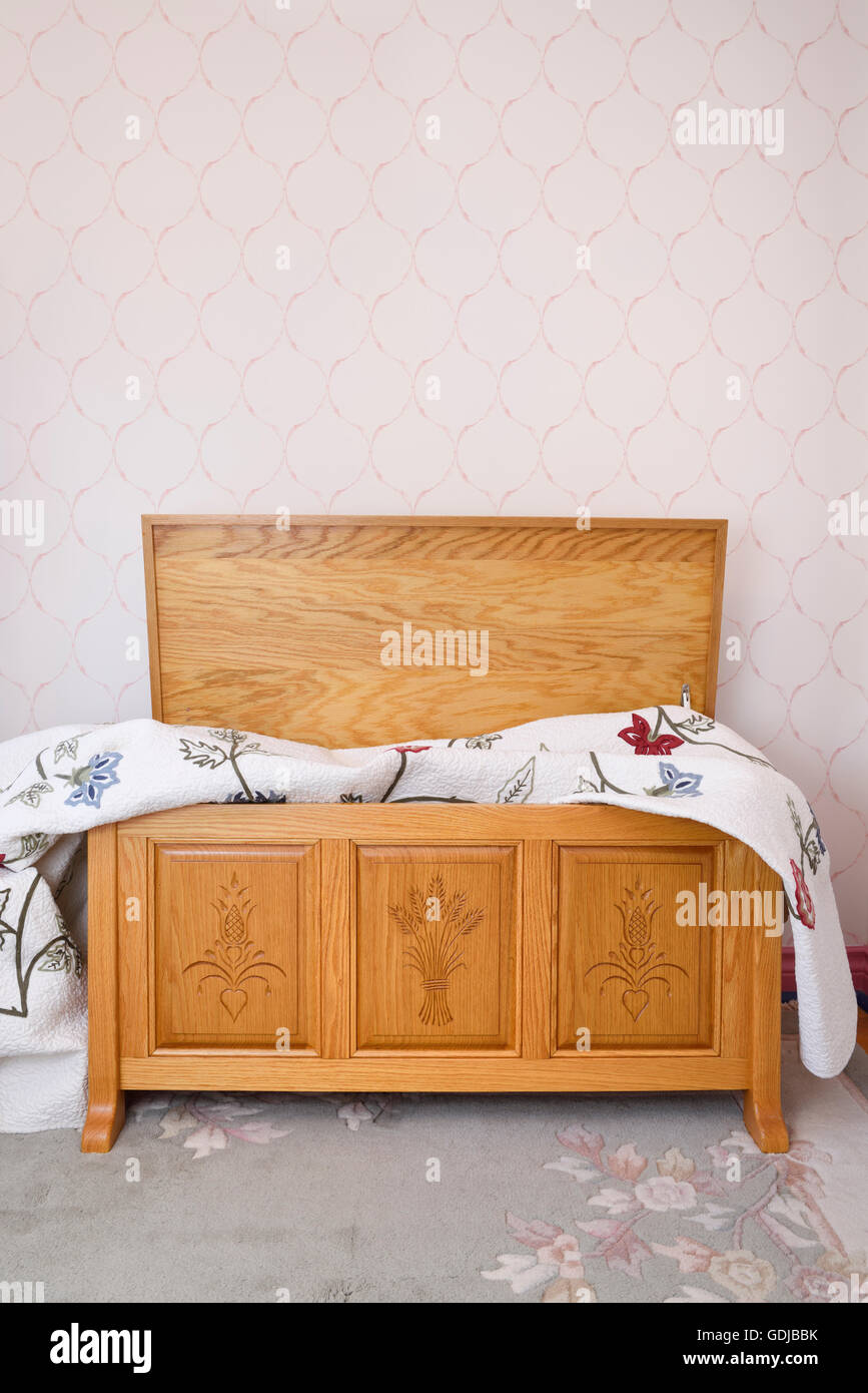 Open hand carved oak cedar chest with blanket in bedroom ...