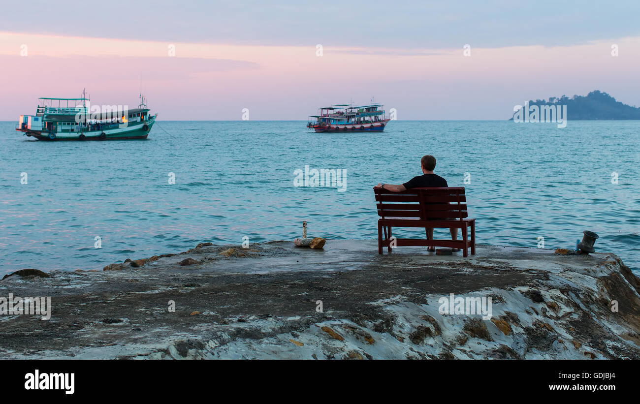 A Lonely Young Man Sitting On The Sea Pier At Dusk
