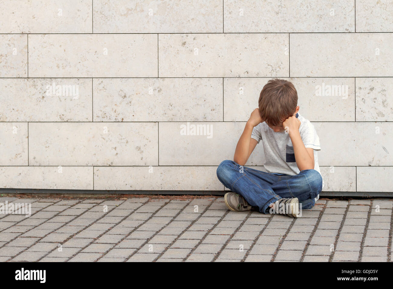 Sad, lonely, unhappy, upset, disappointed tired child sitting alone on the ground Outdoor - Stock Image