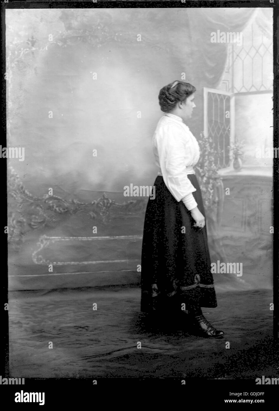 A woman poses in the studio setting. C1910. Photograph by Tony Henshaw - Stock Image