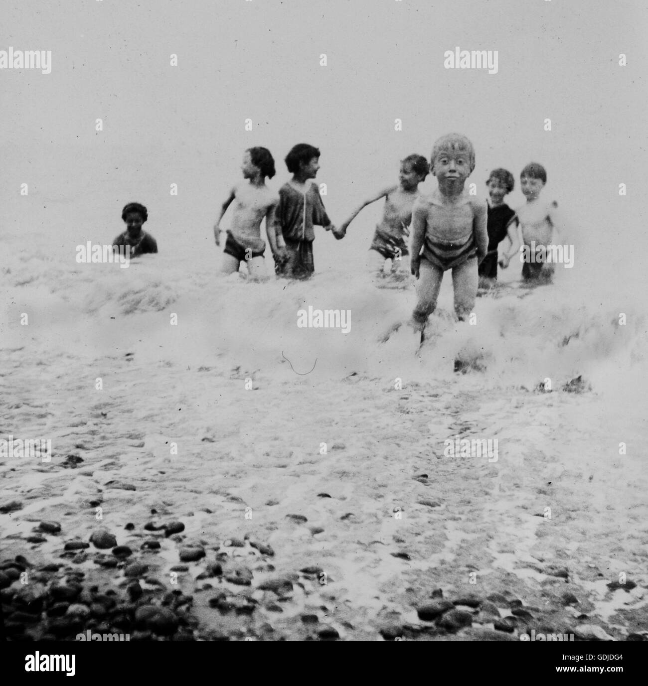 Amateur holiday photo of  happy children playing at the seaside as a small boy pulls a funny face c1899, venue appears - Stock Image
